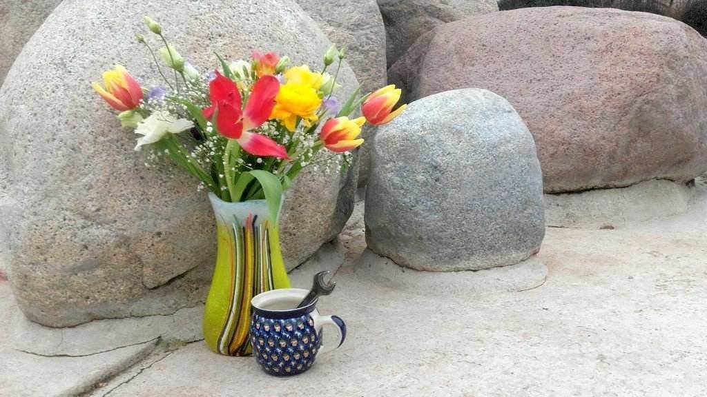 Blumen in Vase und Kaffeetasse mit Schraubenschlüssel vor Findlingsbrunnen in Dresden-Gruna